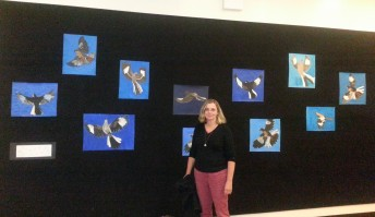 Kristi Pfister with student paintings